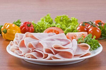 thinly: Thinly sliced ham on a plate, fresh vegetables in the background