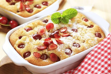 Freshly baked cherry sponge cake in a porcelain casserole dish photo