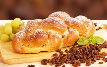 Sweet braided bread sprinkled with icing sugar photo