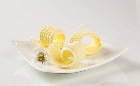 mantequilla: Rizos de mantequilla en un plato de porcelana moderna