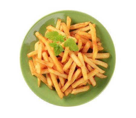 Portion of ready French fries on a green plate photo