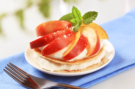 Pancakes with curd cheese topped with slices of fresh peach  photo
