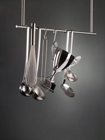 Cup trophy hanging among kitchen utensils on a rack photo