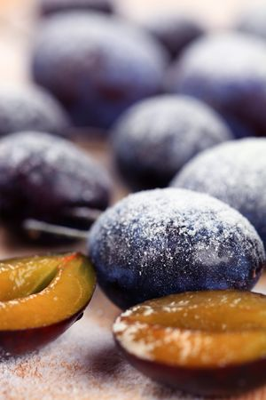 powdered sugar: Ripe plums sprinkled with powdered sugar - detail