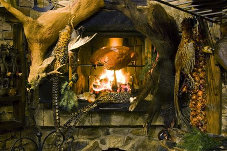 Meat roasting on a fire, venison hanging in front of a fireplace  photo