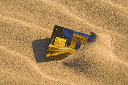 lost money: Close up of a credit card left in the sand