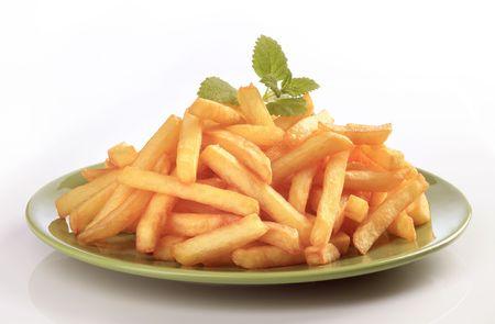 papas fritas: Mont�n de patatas fritas en una placa verde Foto de archivo