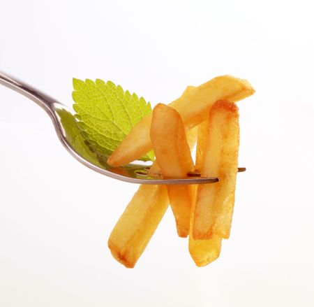 pomme: French fries on a fork against white background