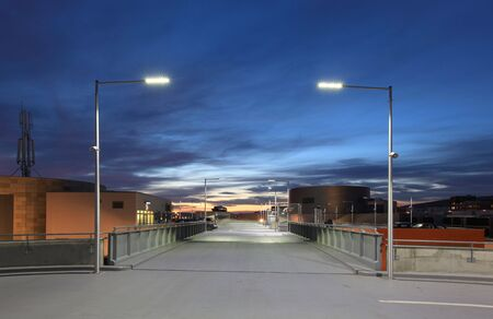Empty car park illuminated by street lights
