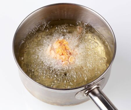 Chicken drumstick coated in corn flakes being deep fried