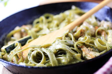 Spinach fettuccine with chicken, basil pesto and cream sauce photo