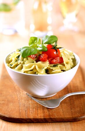 accompaniment: Bowl of bowtie pasta with tomatoes  Stock Photo