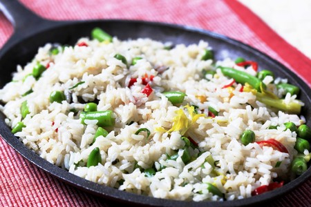 rice grains: Rice and mixed vegetables stir fried in a skillet