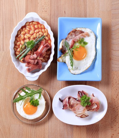 English breakfast of baked beans, sausages, fried egg and bacon photo
