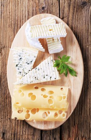 Variety of cheeses on a cutting board photo