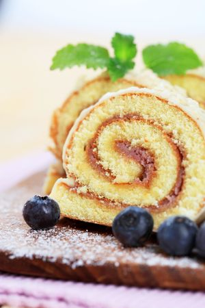 Slices of Swiss roll and fresh blueberries photo