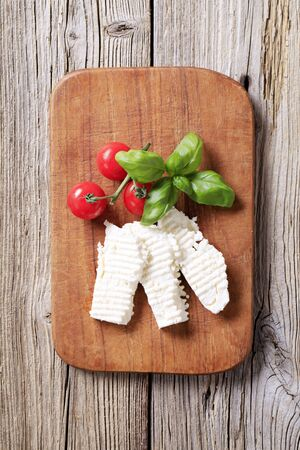 Slices of feta cheese on a cutting board photo