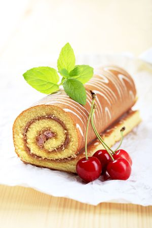 Swiss roll and fresh red cherries - still life photo