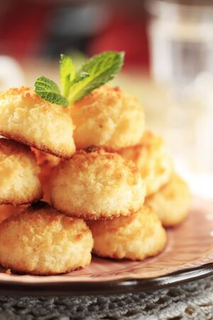 Stack of coconut macaroons on a decorative plate photo