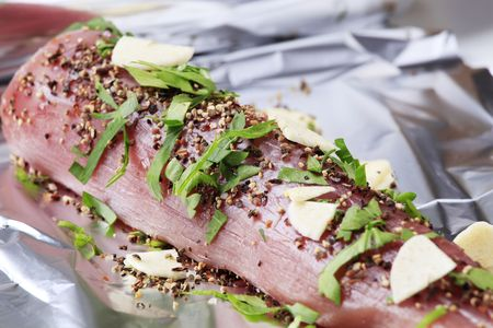 Raw pork tenderloin sprinkled with spices and garlic photo