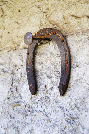 Rusty horseshoe hanging on a nail on a wall photo