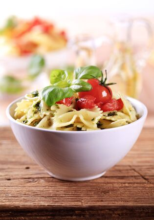 side salad: Bowl of bowtie pasta with pesto and tomato  Stock Photo