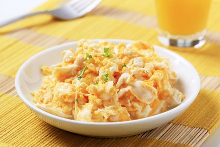 Scrambled eggs and a glass of juice photo