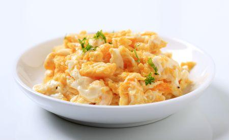 sprinkled: Plate of scrambled eggs sprinkled with fresh parsley