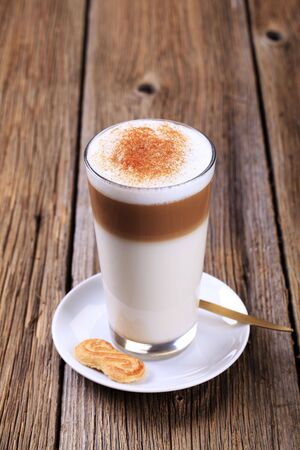 Glass of Latte macchiato with a dusting of nutmeg  photo