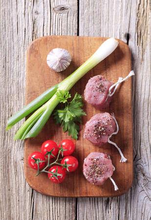 Raw pork filet mignons and fresh vegetables photo