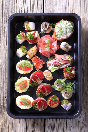 Assortment of hors doeuvre on a black tray photo