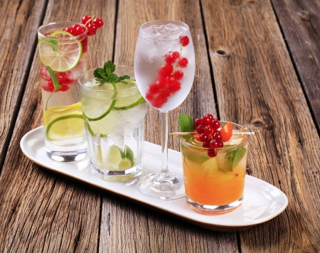 Glasses of iced drinks garnished with fresh fruit photo