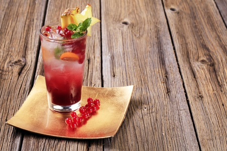 Glass of iced drink garnished with fresh fruit photo