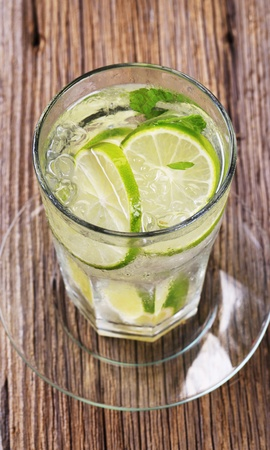 Glass of cold drink with slices of lime photo