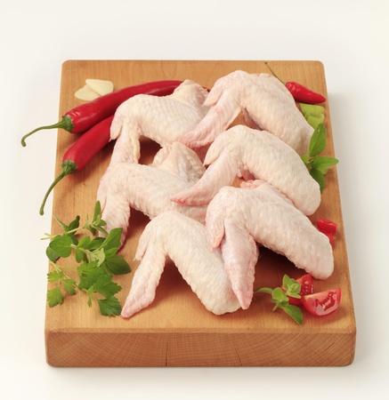 alitas de pollo: Alas de pollo crudo sobre una tabla para cortar