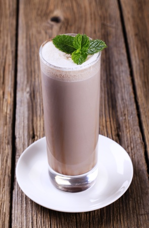 Glass of chocolate milk shake on wooden table photo