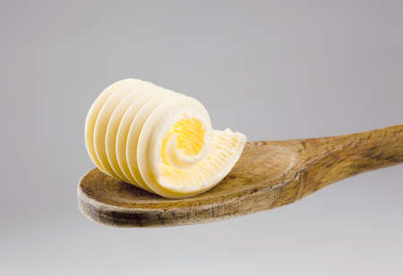 Closeup of a butter curl on a wooden spoon 