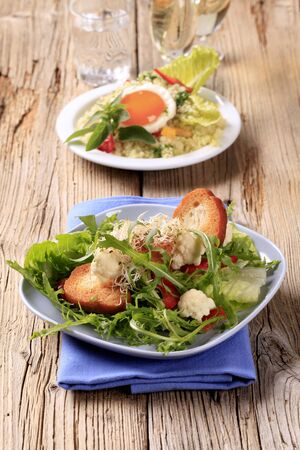 Fresh vegetable salad with crispy bread, couscous salad and fried egg in the background photo