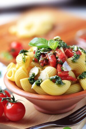 Macaroni with capers, crushed tomatoes and pesto photo