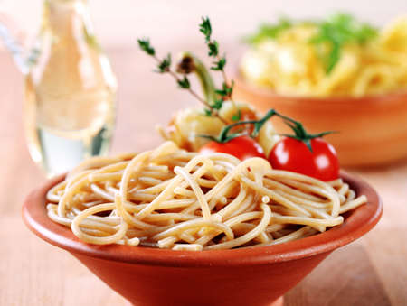 Cooked whole wheat spaghetti in a terracotta bowl photo