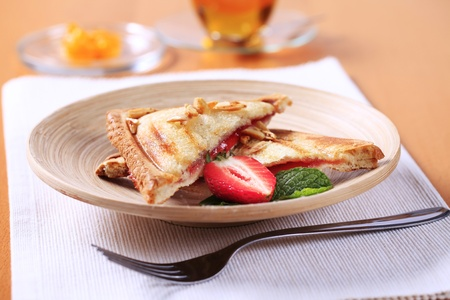toasted sandwich: Toasted sandwich filled with strawberry jam - closeup
