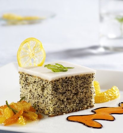 icing: Poppy seed cake with icing garnished with fruit Stock Photo