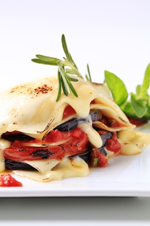 Tomato and aubergine lasagna topped with cheese photo