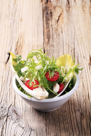Salad greens with tomato and diced feta cheese photo