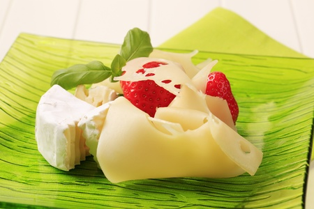 Cheese and fresh strawberries on a plate photo