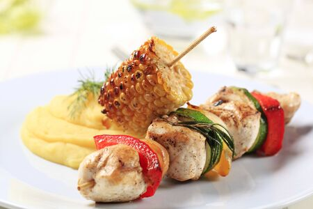 Chicken shish kebab and roasted corn cob with mashed potato photo