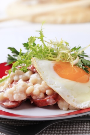 White beans with sausage and fried egg - detail photo