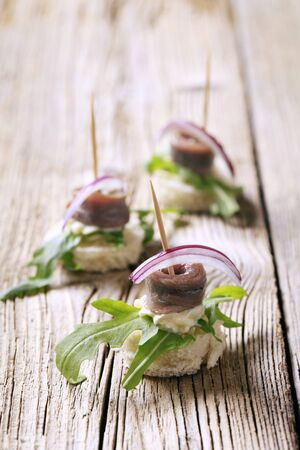 Anchovy canapes garnished with greens and onion photo