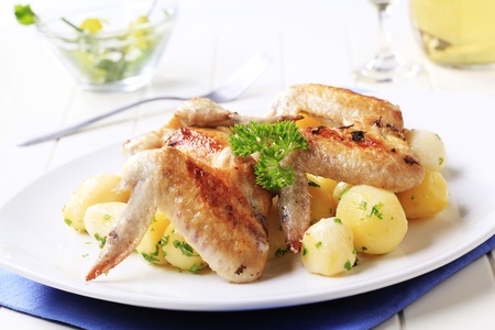 chicken wings: Roasted chicken wings and potatoes - closeup Stock Photo