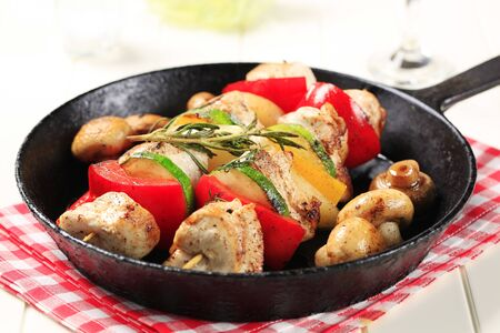 Chicken shish kebabs and mushrooms in a pan  photo